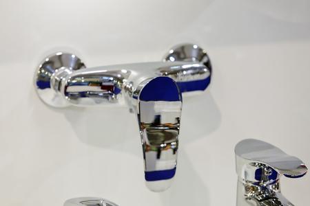 Modern ontwerp van chroomtapkraan voor gootsteen; noteer ondiepe scherptediepte