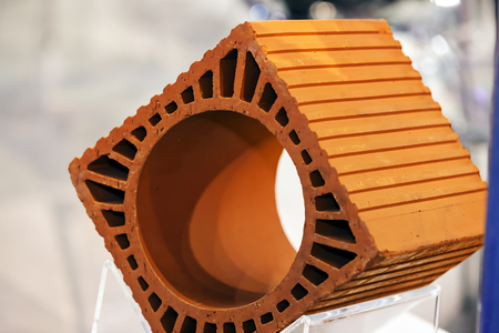 Detail of orange hollow clay block on a stand at construction fair  Stock Photo