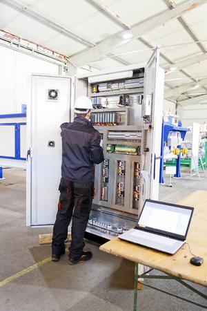 Man werknemer controleert geavanceerd industrieel controlepaneel in de productiehal