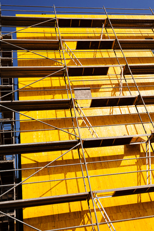 yellow protective tarpaulins and scaffolding on a building