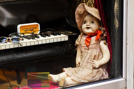 Vintage doll sitting on windowsill