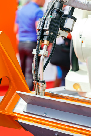 Robotic cutting machine tool for industrial manufacture factory; note shallow depth of field