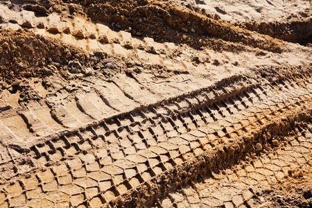 smaller sand with tire tracks in construction Imagens