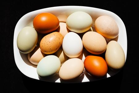 Kleurrijke eieren in witte kom, die op zwarte achtergrond wordt geïsoleerd Stockfoto