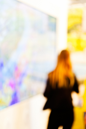 Woman in black suit tries showpiece at technology expo; blurred 100% Stock Photo