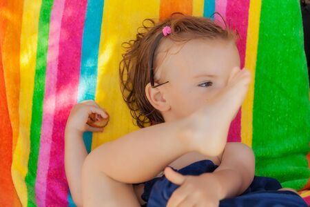 baby eating a donut on the beach, note shallow depth of field