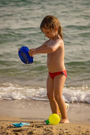 the child is playing on a sandy beach