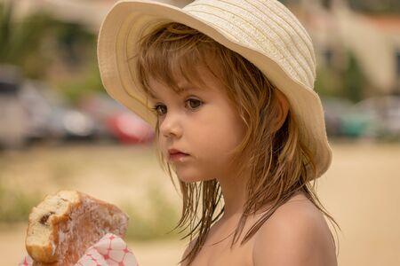 Girl eating a donut on the beach