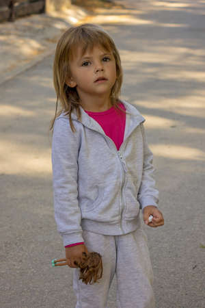 little girl walks around the city park in the spring