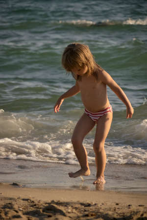 little girl running in the shallow water at the seaside Banco de Imagens