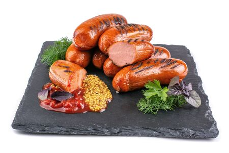 grilled sausages, mustard seeds, ketchup, Basil and parsley on a stone tray, white isolated background, free space