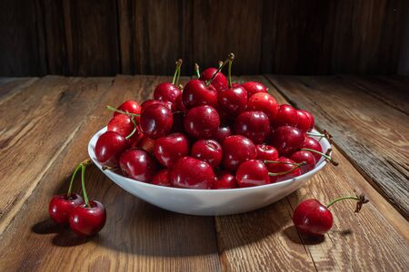 fresh, juicy cherries in a plate on a wooden table close-up, rustic style, horizontal view