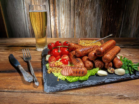 grilled sausages, cherry tomatoes, garlic, dill, a glass of beer, mustard sauce, fresh herbs on a wooden table, rustic style, horizontal view 免版税图像