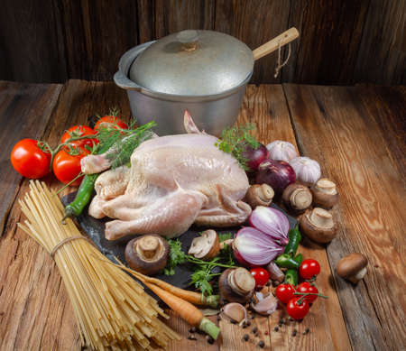 A set of fresh products for cooking chicken dishes.Chicken, carrots, mushrooms, onions, Bay leaf, tomatoes, pepper, dill, parsley, pasta, cast-iron pot, on a wooden table, close-up, top view