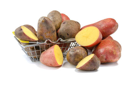 Raw pink whole and cut potato tubers in a shopping basket on a white isolated background.Potatoes in the skin.