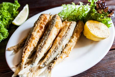 Fried small capelin on a plate on a wooden table. A good beer snack.