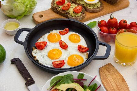 Pan of fried eggs with fresh tomato and bread on over white background, top view