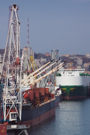 Several ships unloading by cranes with a panorama of the city in the backgroundr Stock Photo - 13097024
