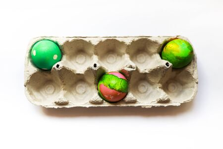 three self-decorated easter eggs in vibrant green colour placed separately in a tray to demonstrate concept of social distancing Reklamní fotografie