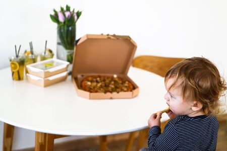 little boy sitting at the table eating pizza, food in to go boxes on the table, stay home, food delivery concept Reklamní fotografie