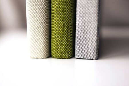 three textile photobooks standing on the table, close up side cover view, design mock up Stock Photo