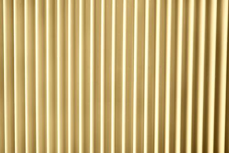 Close up of a radiator in sunlight yellow trendy color. Abstract pastel geometric background.