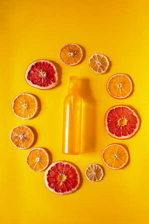 Flat lay with bottle of spay and dry oranges. Mono color. Composition with organic cosmetic on orange background