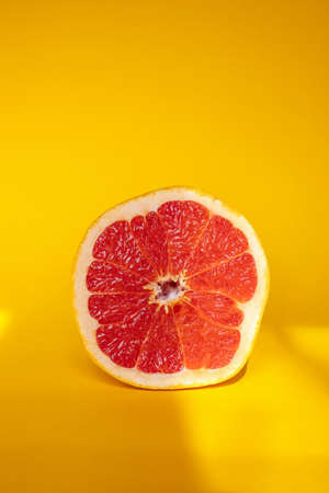 Half of grapefruit on orange background with sun stripes