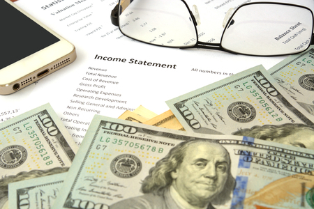 income statement report on the table with money phone and glass