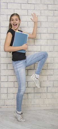 briks: Happy joyful young girl with books, jumping, briks buckground