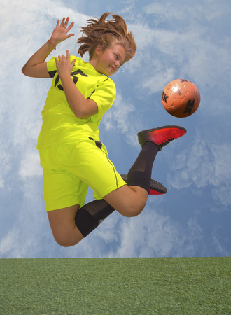 futbol infantil: Female Soccer Player jump with ball. Blue sky background