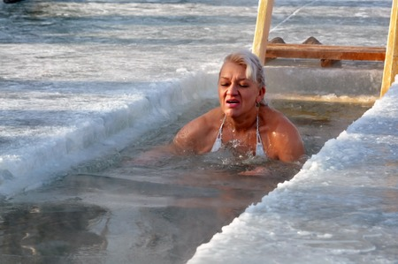 Woman commits ritual bath for Epiphany. Editorial