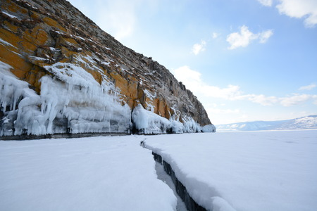 Winter landscape. Blue ice and snow, rock and coast of lake Baikal Stock Photo