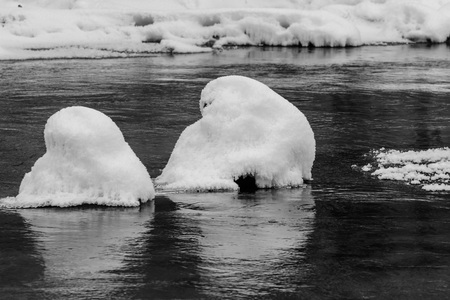 Winter landscape with non-freezing river and snow made the form of round convex hats. Фото со стока