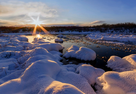 Suset winter landscape with non-freezing river and snow made the form of round convex hats.