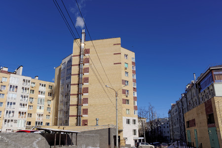 heats: Nizhny Novgorod, Russia. - March 18.2016. Modern multi-story brick apartment house with its own boiler. In recent cold days in early spring boiler heats the house.