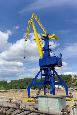 Gorodets, Russia. - June 2.2016. Blue portal crane with a yellow arrow on the cargo wharf in Gorodets about Gateway