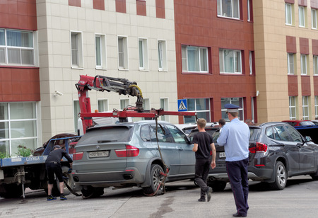 parking violation: Nizhny Novgorod, Russia. - July 14.2016. The municipal tow truck evacuates wrong parked car in the Maxim Gorky street 117.