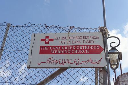 Kfar Kana, Israel. - February 17.2017. The tablet with the inscription The Cana Creek Orthodox Wedding Church in Greek, English and Arabic.