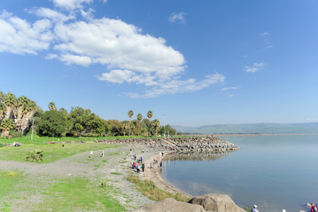 Tourists are walking on the shore of the Sea of Galilee in Israel.