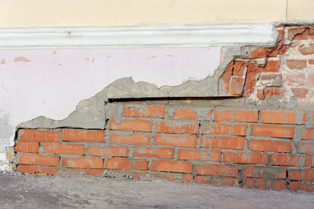 The collapsed corner of the old brick house is repaired with a fresh masonry of red brick.
