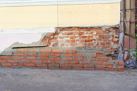 The collapsed corner of the old brick house is repaired with a fresh masonry of red brick. The photo shows a fragment of the wall of the house.