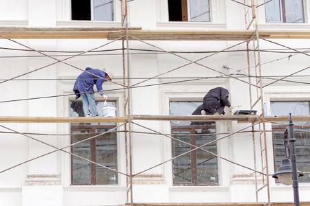 니즈니 노브 고로드, 러시아. - October 03.2017. Rozhdestvenskaya street 42에있는 Nizhny Novgorod 지역의 피부 진드기 치료실의 수리. 비계 작업자가 벽을 페인트합니