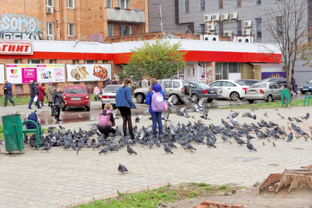 Nizhny Novgorod, Russia. - October 06.2017. Children teens feed a large flock of pigeons on the prospectus of the 70th anniversary of October