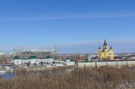 Nizhny Novgorod, Russia. - March 14.2017 The Cathedral of Alexander Nevsky and the construction of a football stadium. View from the Kanavinsky Bridge.