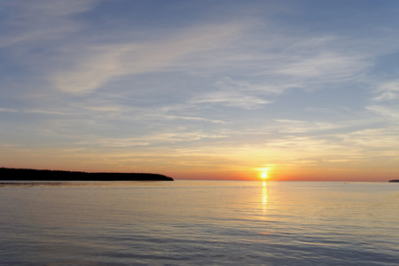 A view of the calm golden sunset on the river with the sun reflected in it, Volga, Russia. Stock Photo