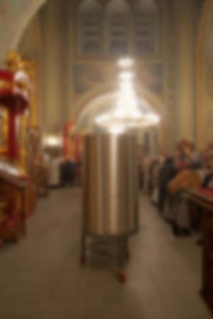 Metal tanks with water in the church for the Epiphany. Soon a water-moleben will be held and the water in them will become a saint. Specially defocused image with blurred image.
