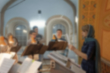 The regent directs the singing of the church choir during the Liturgy. Specially defocused image with blurred image. Archivio Fotografico