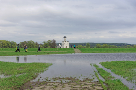 Vladimir region, Russia. - May 06.2018. Path along a green field to the Church of the Intercession on the Nerl. A long narrow path paved with gray stone in some places flooded with water. Editorial
