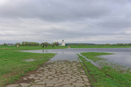 Vladimir region, Russia. - May 06.2018. Path along a green field to the Church of the Intercession on the Nerl. A long narrow path paved with gray stone in some places flooded with water. Редакционное